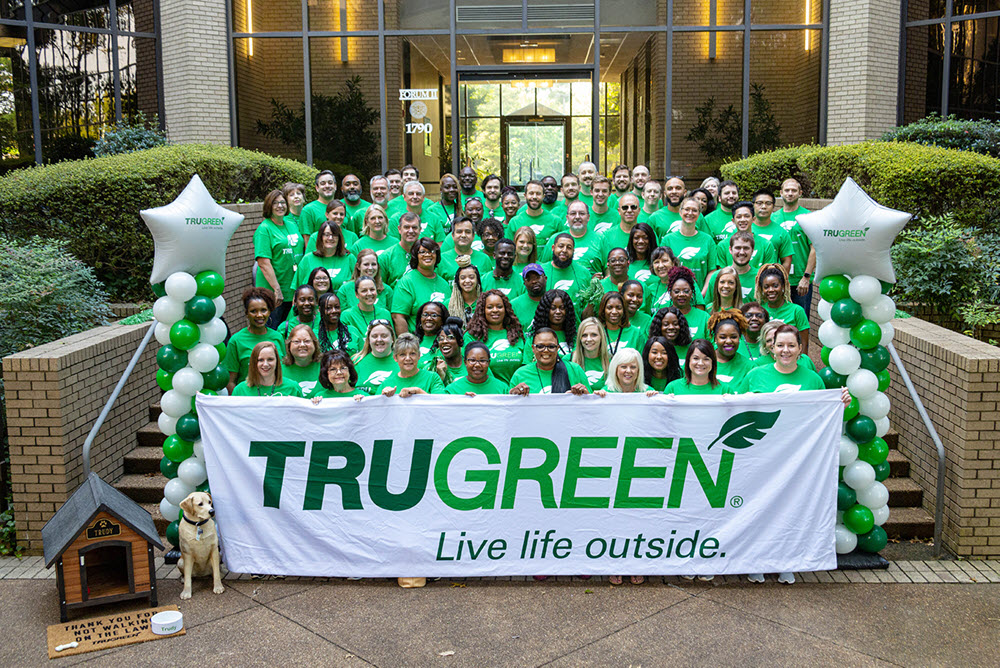 Trugreen employees holding company banner in front of headquarters