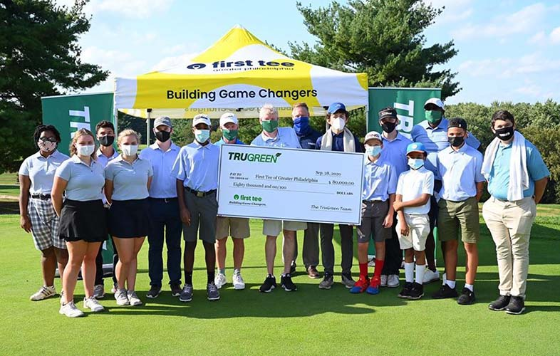 First Tee event  - golfers holding giant check