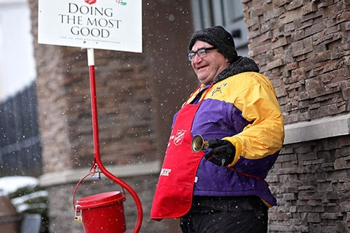 <p>Salvation Army bell ringer smiling</p>